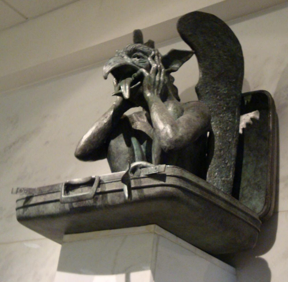Gargoyle sits in suitcase sticking his tongue out at the Denver New World Airport DIA